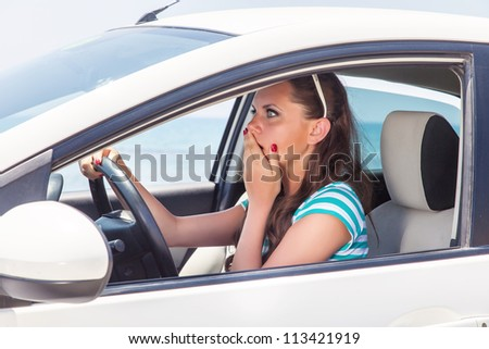 A scared beautiful woman is in the car - stock photo