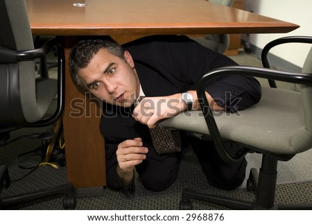A Scared Businessman Hiding Under The Table Stock Photo