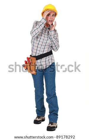 A scared female construction worker. - stock photo