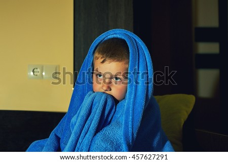 a scared little boy afraid in bed at night , childhood fears - stock photo