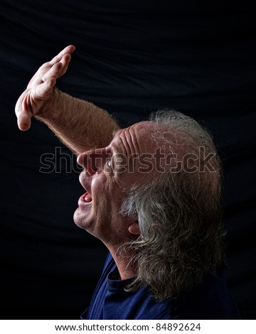 A scared older man his his hand up in front of his face trying to hide and is screaming out in fear. - stock photo