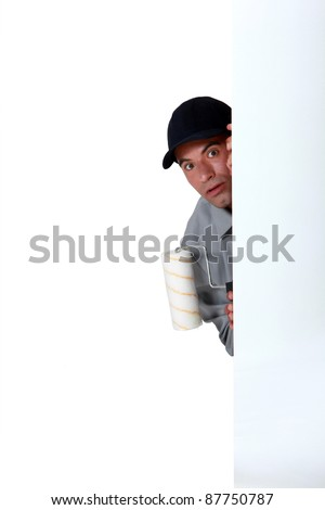 A scared painter hiding behind a wall. - stock photo