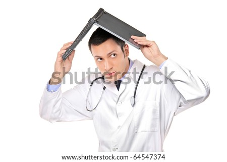 A scared young doctor covering his head with an open laptop isolated on white background - stock photo