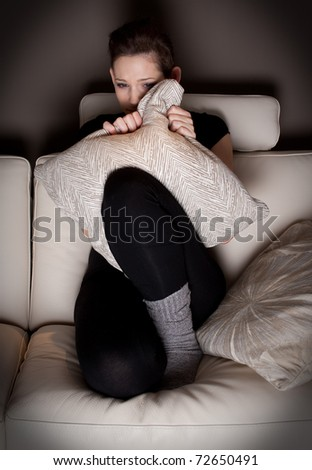 A scared young woman watching a horror movie at home - stock photo
