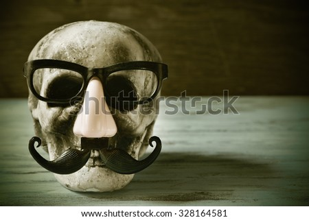 a scary and funny skull with eyeglasses, fake nose and mustache on a rustic wooden surface, with a filter effect - stock photo