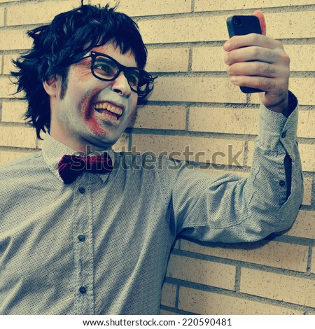 a scary hipster zombie taking a selfie of himself with a smartphone, with a retro effect - stock photo