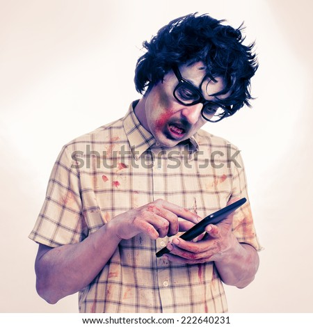 a scary hipster zombie using a tablet computer, with a filter effect - stock photo
