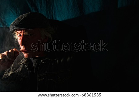 a scary looking man is sitting in the dark smoking a pipe and looking menacingly at the viewer. - stock photo