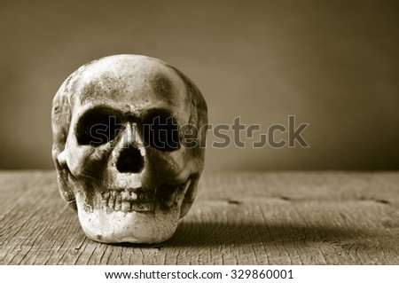 a scary skull on a rustic wooden surface, in sepia toning, with a dramatic effect - stock photo