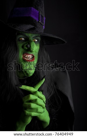 A scary witch, contemplating evil thoughts.  Low key lighting. - stock photo
