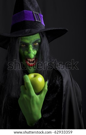 A scary witch holding a green apple. Isolated on black. - stock photo