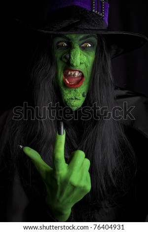 A scary witch, signaling come here. Low key lighting. - stock photo