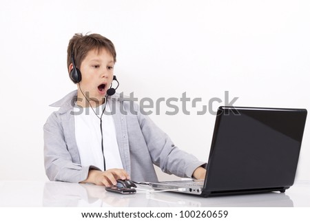A scary young boy with a headset  looks something on the Internet. - stock photo