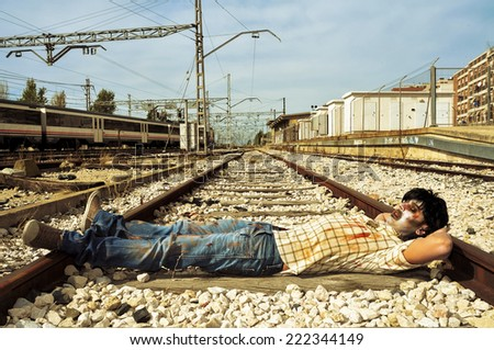 a scary zombie taking a nap at abandoned railroad tracks - stock photo
