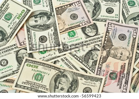A scattered pile of hundred, one, fifty, twenty dollar bills. - stock photo