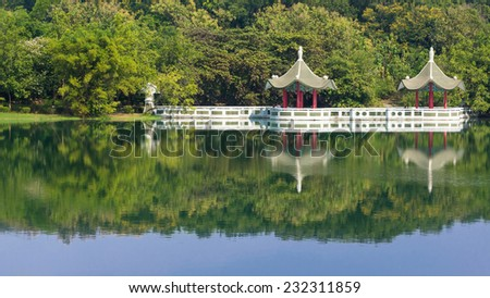 A Scene of Cheng Ching Lake With Two Chinese Pavilions by The Lake. The Water Reflect Green Forest , The Pavilions And Blue Sky. With Tourists Walking by The Lake - stock photo