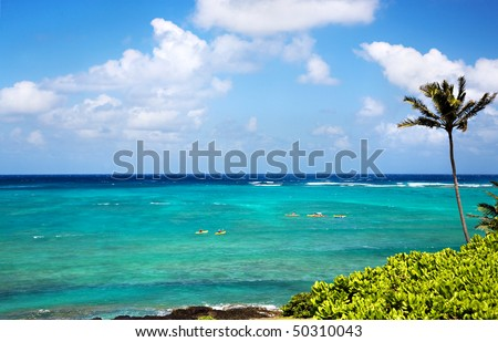 A scene overlooking the ocean and sky in Kailua Hawaii, with incredible shades of blue, fluffy white clouds and some colorful yellow and red kayaks - stock photo