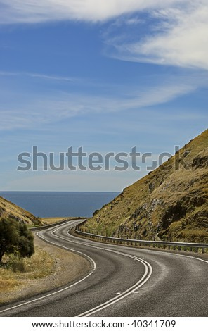 A scenic and winding coastal road between mountains, leading to the ocean. - stock photo