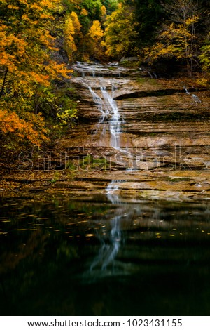 A scenic, autumn view of Buttermilk Falls at Buttermilk Falls State Park in Ithaca, New York.