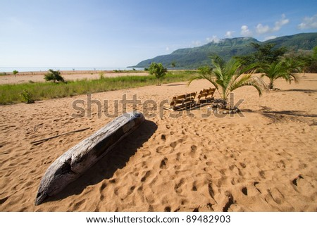 A scenic beach next to lake malawi with palm trees, soft sand and a dugout canoe - stock photo