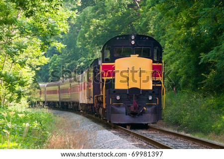 A scenic passenger train rounds a curve in a forested area - stock photo