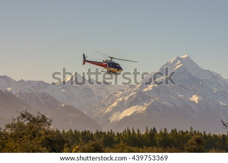 A scenic tour helicopter flies over the Southern Alps mountain range at Mount Cook National Park, New Zealand on April 16, 2015 . The setting sun casts orange hues on snow capped mountain.
