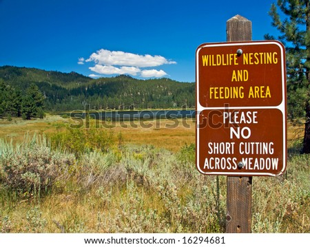 A scenic view of a pristine lake, mountains and forest with a sign to protect the wildlife