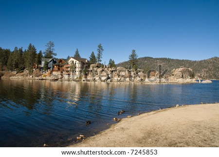 A scenic view of lakefront real estate during a cold, sunny day in the mountains. - stock photo