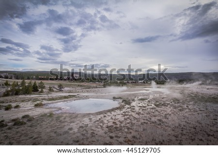 A scenic view of landscape with hot springs and cloudy sky, Upper Geyser Basin, Yellowstone National Park - stock photo