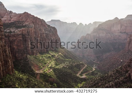A scenic view of the winding road between canyons, from Canyon Overlook Trail, Zion National Park, with light ray  - stock photo