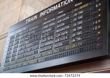 A schedule board in a train station with information telling the time and destinations for travelers. - stock photo