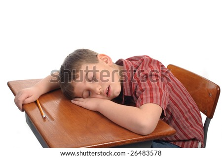 A school boy resting at his desk - stock photo
