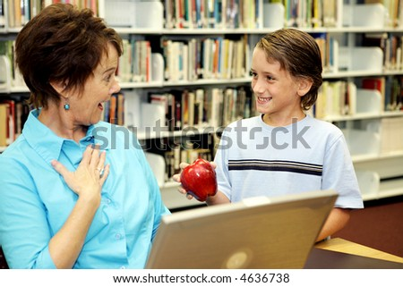 A school boy surprising his teacher with an apple. - stock photo