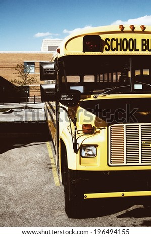 A school bus parked in front of a building. - stock photo