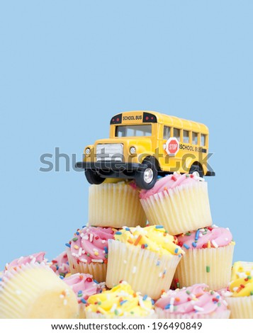 A school bus sitting on top a pile of cupcakes. - stock photo