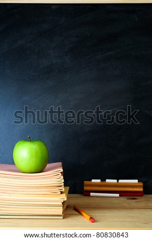 A school chalkboard and teacher's desk with stack of exercise books and an apple. Copy space on blackboard.  Portrait (vertical) orientation. - stock photo