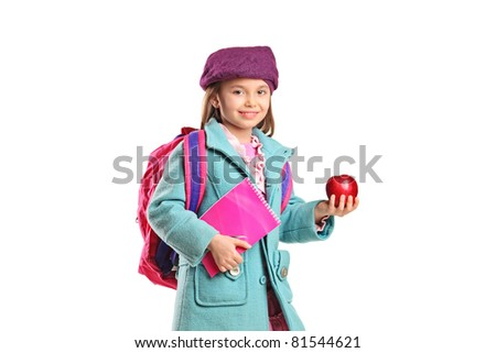 A school girl with backpack holding notebook and red apple isolated on white background