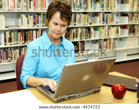 A school librarian frowns as she reviews students on-line activity. - stock photo