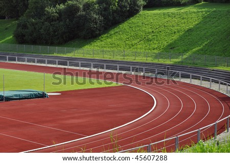 A school's running track and football field with high jump - stock photo