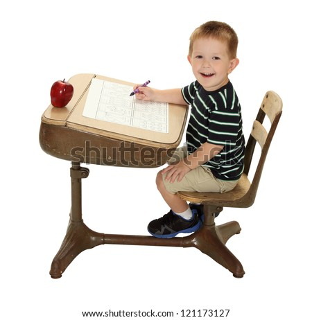 A school student is happy at his desk writing with a crayon and apple for the teacher