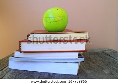 A school teacher's desk with stack of exercise books and apple . A blank blackboard in soft focus background provides copy space.