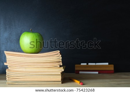 A school teacher's desk with stack of exercise books and apple in left frame. A blank blackboard in soft focus background provides copy space. - stock photo