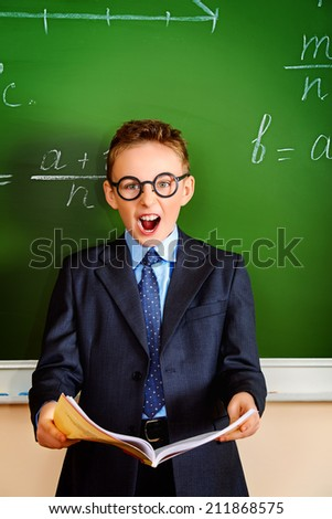 A schoolboy screams violently at the blackboard in the classroom. Education.