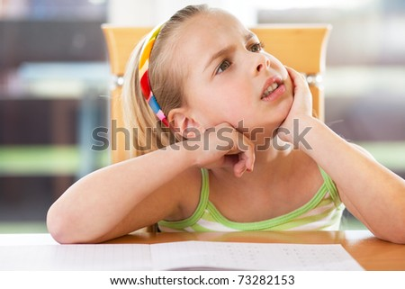 a schoolgirl despairing in front of her math problems. - stock photo