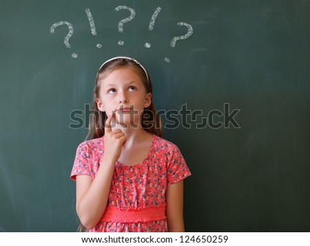 a schoolgirl thoughtful  in front of a blackboard with copy space - stock photo