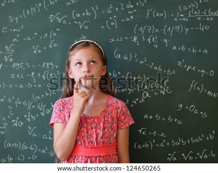 a schoolgirl thoughtful  in front of a blackboard with many mathematical formulas - stock photo