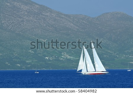 a schooner under full sail leans over mountains in the background - stock photo