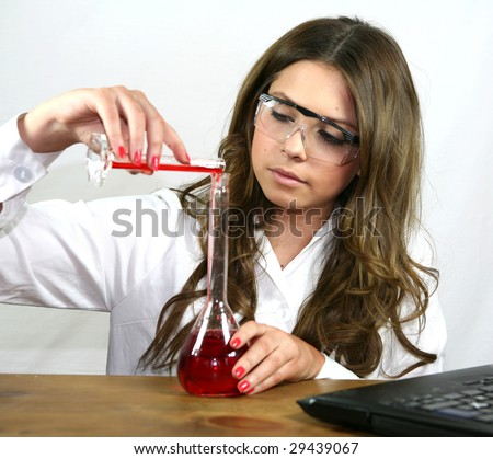 A science student pours a red solution - stock photo