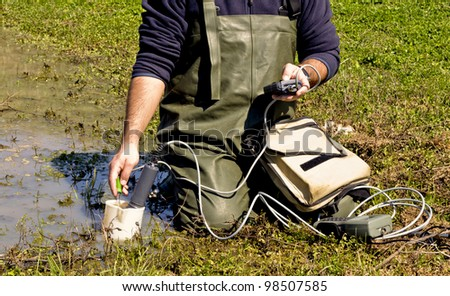 A scientist measuring environmental water quality in a wetland - stock photo