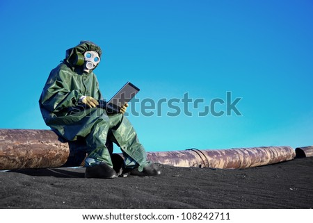 A scientist working with a laptop on a chemically contaminated area - stock photo